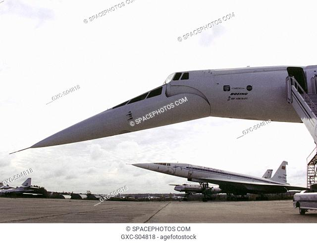 A Tupolev Tu-144D supersonic jetliner is framed by the drooped nose and forward fuselage of the Tu-144LL supersonic flying laboratory at the Zhukovsky Air...