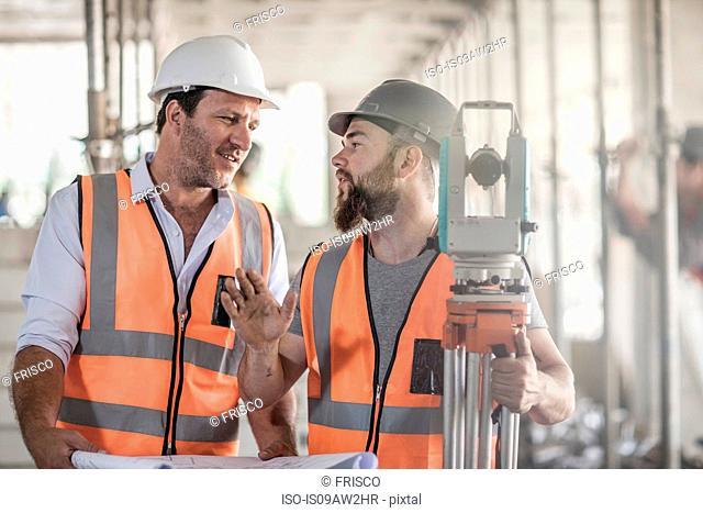 Surveyor explaining to site foreman on construction site