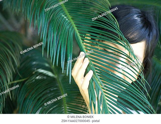 Woman standing amongst palm leaves, head and shoulders