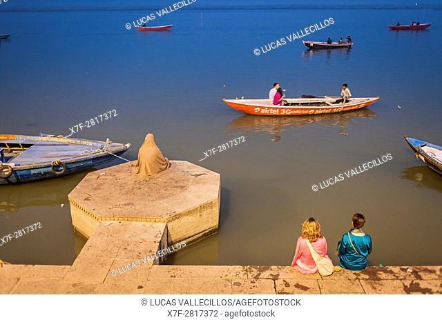 Man praying and tourists, in Lalita ghat, Ganges river, Varanasi, Uttar Pradesh, India