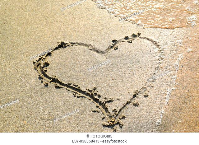 Heart drawn on the beach sand. heart symbol on the sand washed by the sea wave