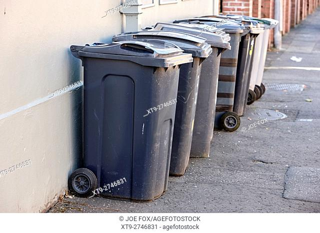 line of wheelie refuse bins left out on the pavement for collection