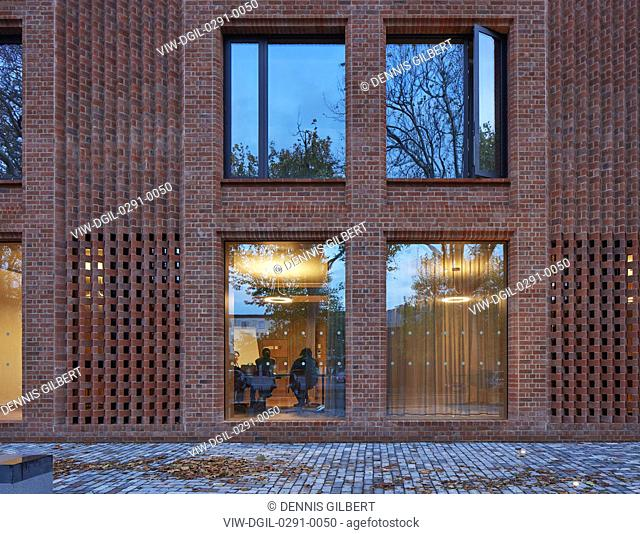 Entrance detail with perforated brickwork and window reflections. Newnham College, Cambridge, Cambridge, United Kingdom. Architect: Walters and Cohen Ltd, 2018