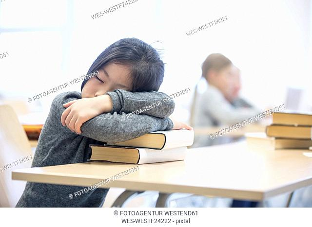 Schoolgirl sleeping on stack of books on table in school