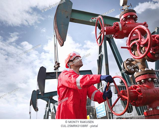 Worker turning valve on oil well