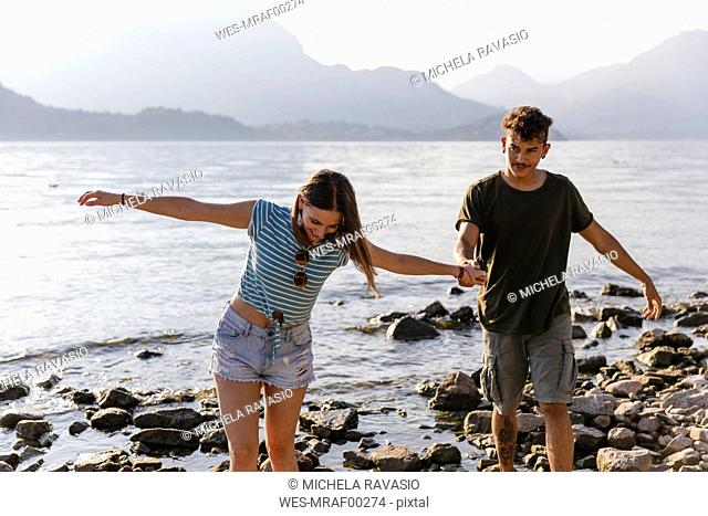 Young couple walking hand in hand at the lakeside