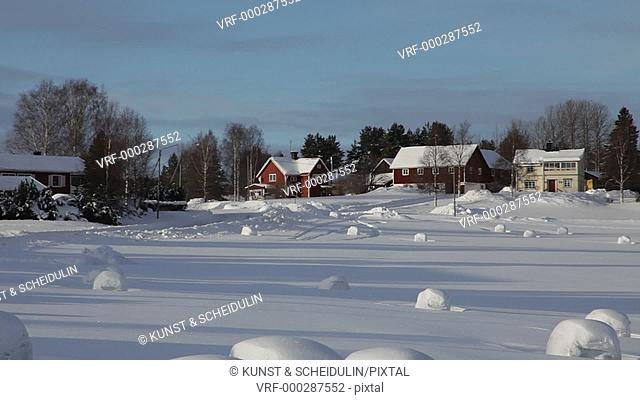 Panning shot covering a Swedish village in winter. A row of houses are standing on top of a hill, the fields below are dotted with plastic covered hay rolls
