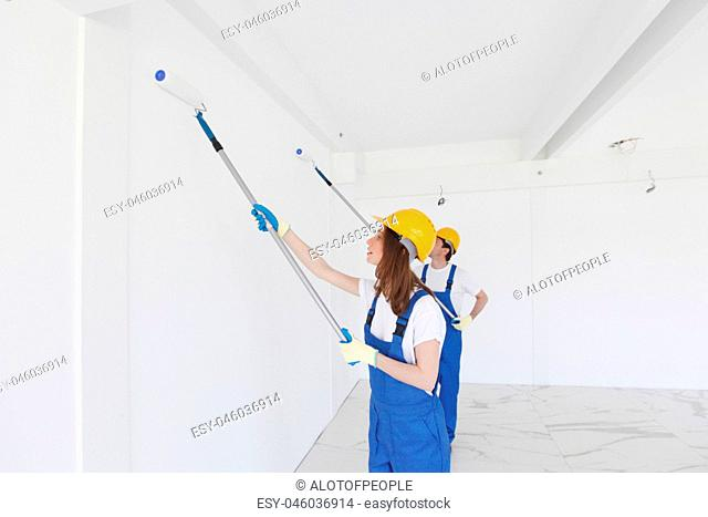 workmen painting wall