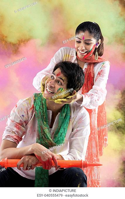 Woman putting colour on a man's face