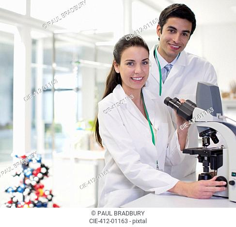 Portrait of smiling scientists using microscope in laboratory