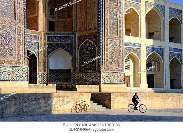 Man on a bicycle in front of Mir-i-Arab Madrasa. Uzbekistan, Bukhara