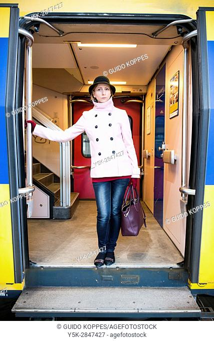 Breda, Netherlands. Young adult woman waiting inside the door of her intercity train for departure to her work assignment as a music teacher