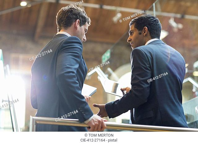 Businessmen with digital tablet talking in office