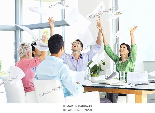 Business people tossing papers in air in meeting