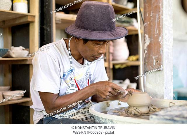 Man in workshop working on pottery