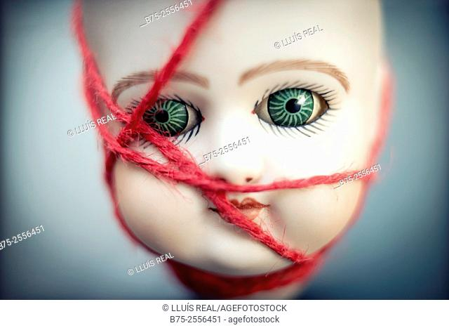 Head of antique porcelain doll tied with a red rope
