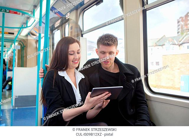 Businesswoman and businessman using digital tablet in Docklands Light Railway train, London