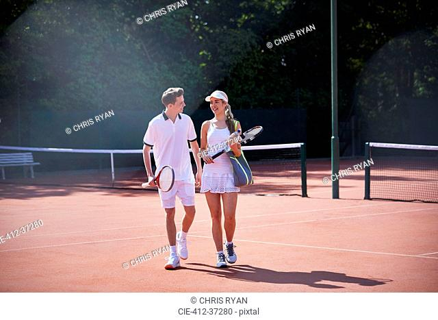 Tennis player couple walking, carrying tennis rackets on sunny clay tennis court