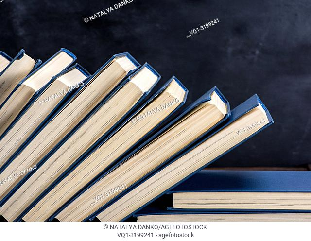 uneven pile of books in the blue cover, black background, copy space