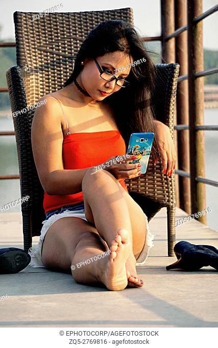Young woman sitting relaxed on the floor and looking at mobile, Pune, Maharashtra