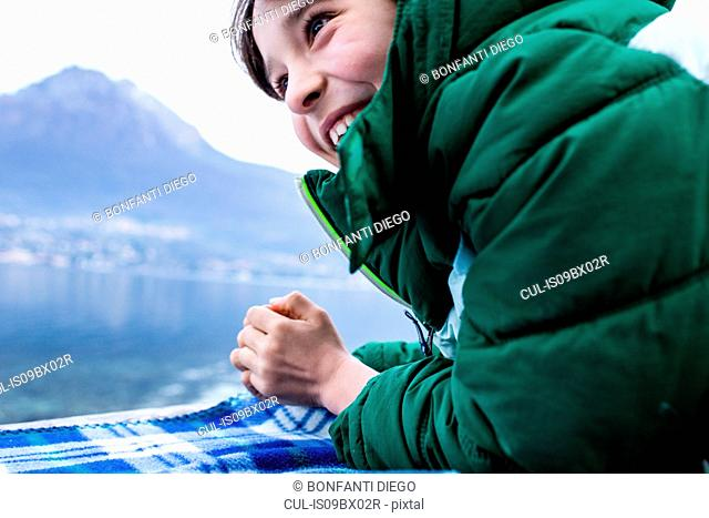 Boy in green anorak lying on picnic blanket by lakeside, cropped, Lake Como, Onno, Lombardy, Italy