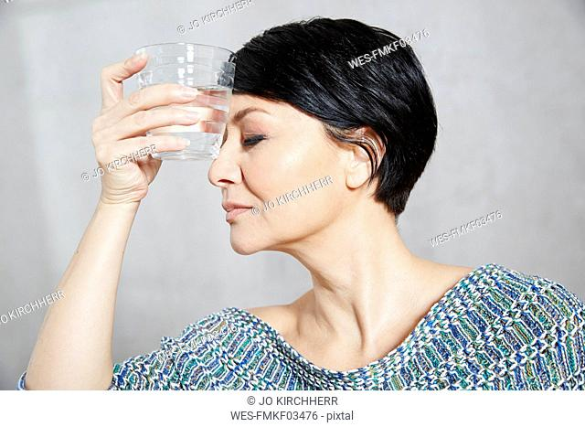 Woman holding glass of water to her forehead