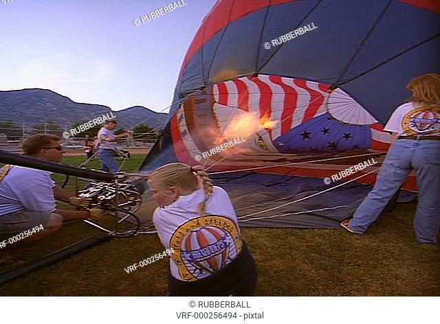 wide shot as group of people fill their balloon with air in preparation for a take off