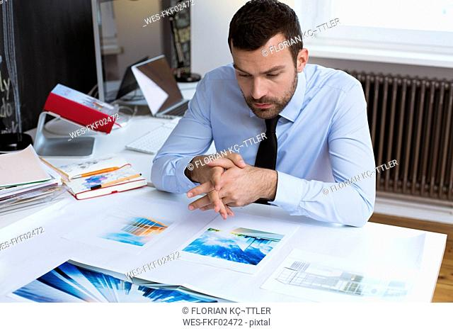 Businessman at desk in office looking at printouts