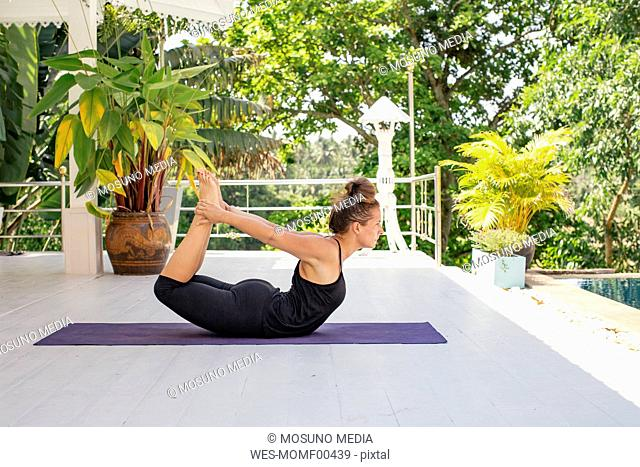 Woman practicing yoga on terrace
