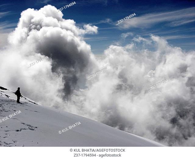 A lone climber stands on fresh snow near the top of Mount Kilimanjaro at 5900 meters 19000 feet above sea level as a bank of clouds rises above the ridge