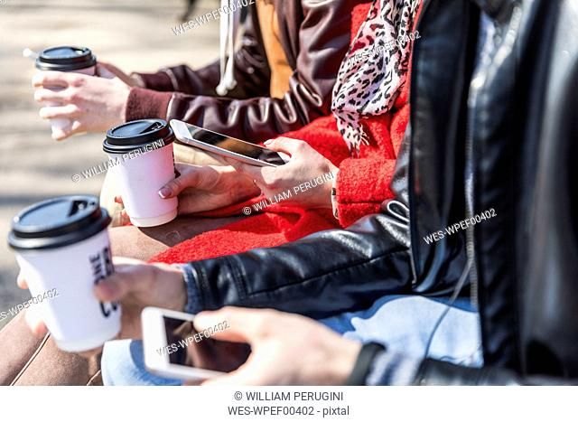 Russia, Moscow, details of three friends holding smartphones and coffee to go