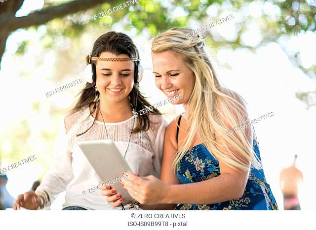 Two young female friends sitting under tree using digital tablet and listening to headphones