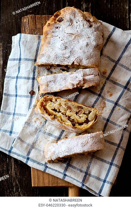 Sliced fresh baked homemade apple strudel over cutting board on old wooden background. Dark rustic style. Natural day light. Top view