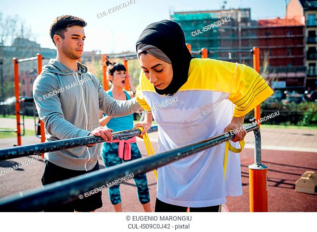 Calisthenics class at outdoor gym, male trainer encouraging young woman on parallel bars