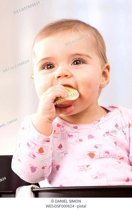 Portrait of baby girl eating an apple
