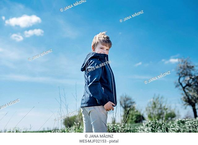 Smiling boy standing against blue sky