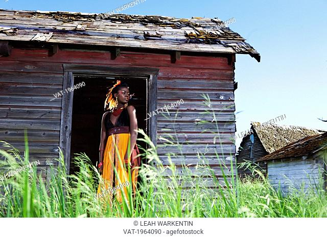 a young woman in a colourful dress, makeup and accessories standing in the doorway of a weathered shed, leduc, alberta, canada
