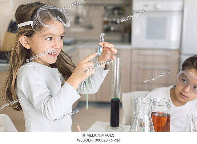 Smiling girl holding test tube at home