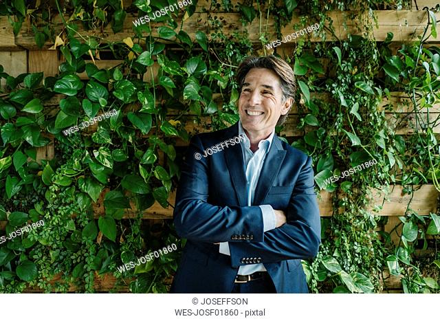 Smiling businessman in green office