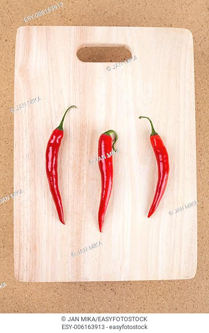 Fresh raw red hot chili peppers on chopping board