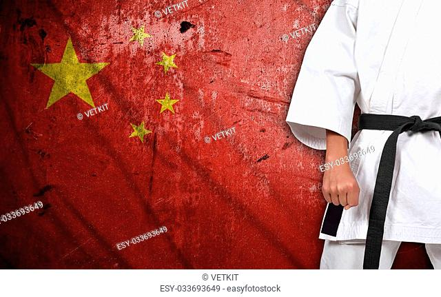 Karate boy in kimono on china flag background