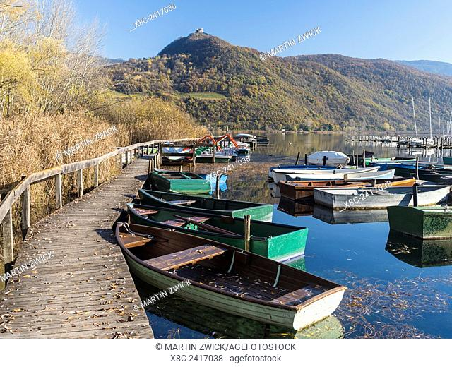Lake Kalterer See (Lago di Caldaro) during autumn. Lake shore with jetty and small boats. Europe, Central Europe, South Tyrol, Italy