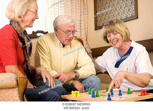 Senior couple and nurse playing ludo together, Bavaria, Germany