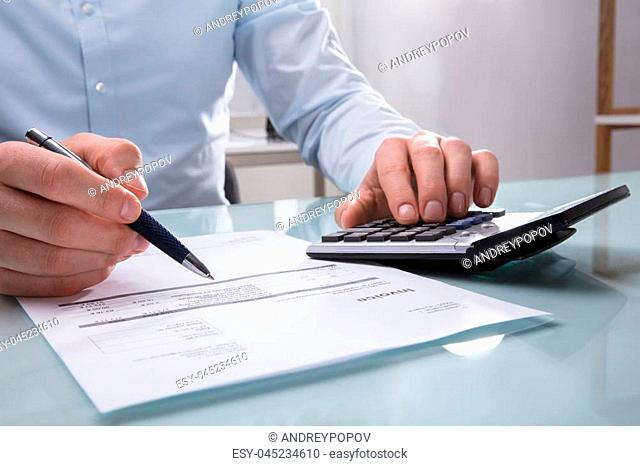 Photo Of Businessperson's Hand Calculating Invoice With Calculator