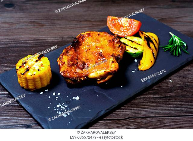 juicy grilled chicken with vegetables on a basalt slab