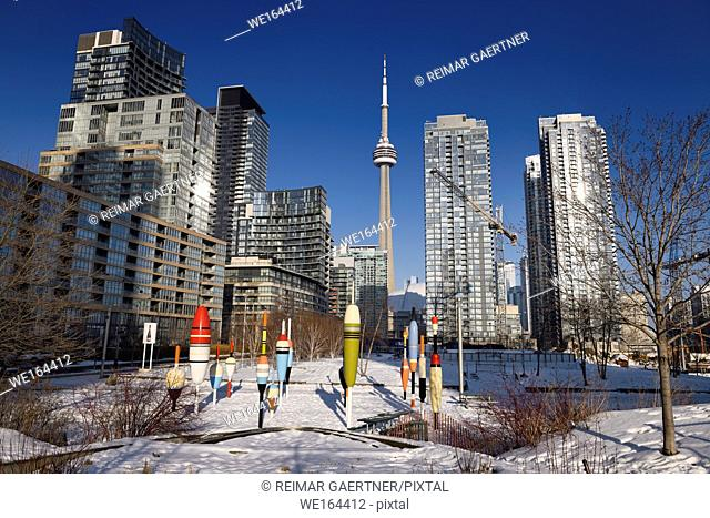 Concord CityPlace now Canoe Landing Park with Fishing Bobbers art in downtown Toronto in winter with CN tower and blue sky