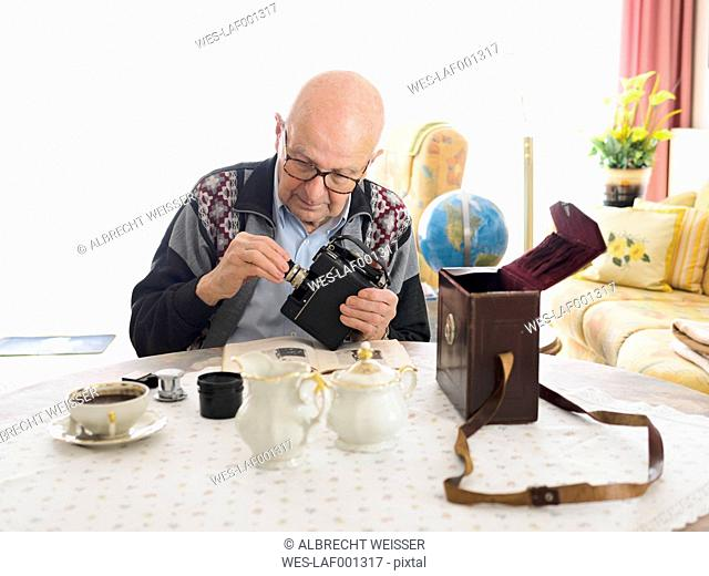 Old man sitting at table dealing with old camera