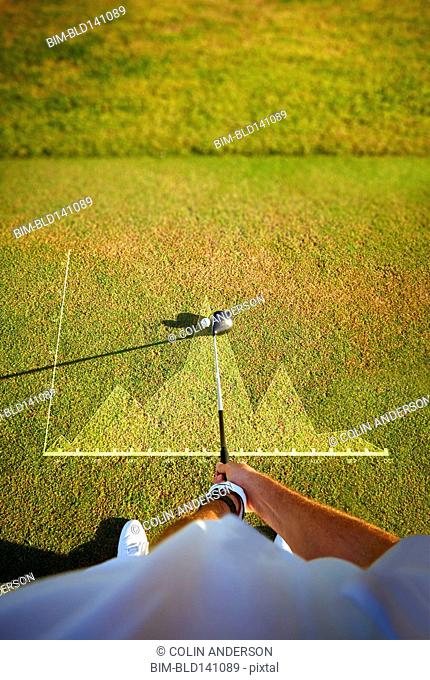 High angle view of Caucasian golfer holding club at ball over graph