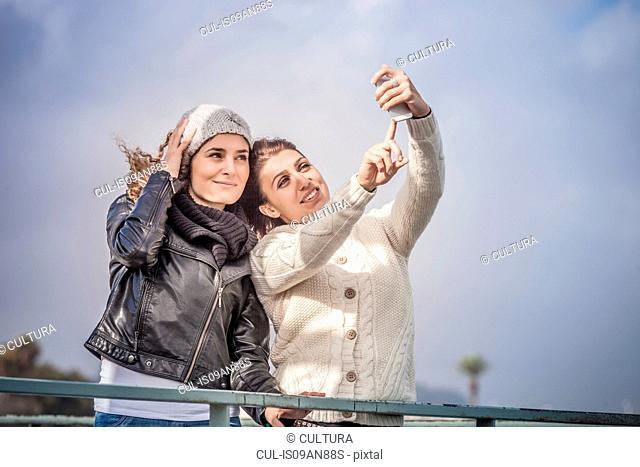 Two young women friends using touchscreen for smartphone selfie at coast