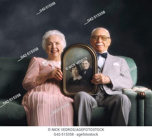 Elderly couple holding photo from when they were just married